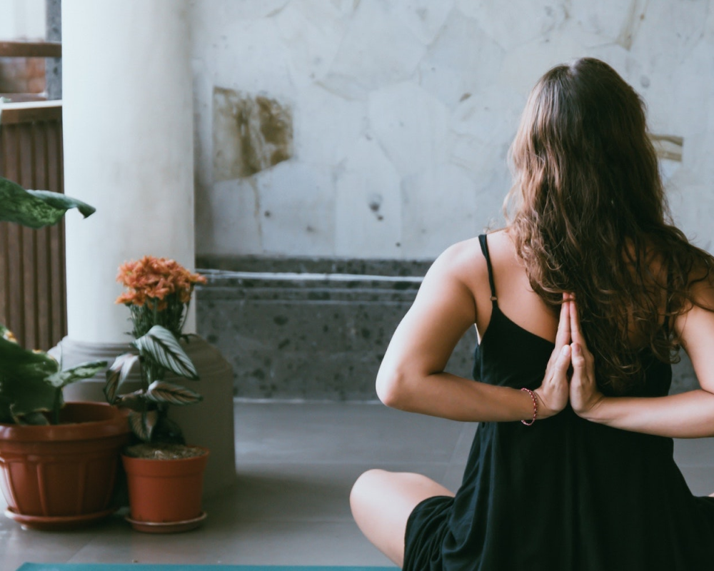 woman sitting with reversed namaste mudra