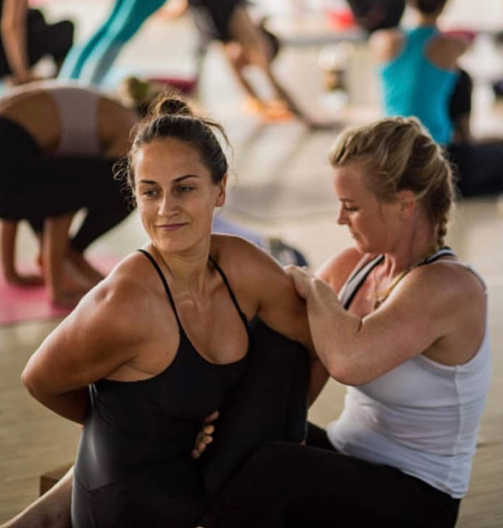 Yoga teacher Jenna Naik assisting seated twist