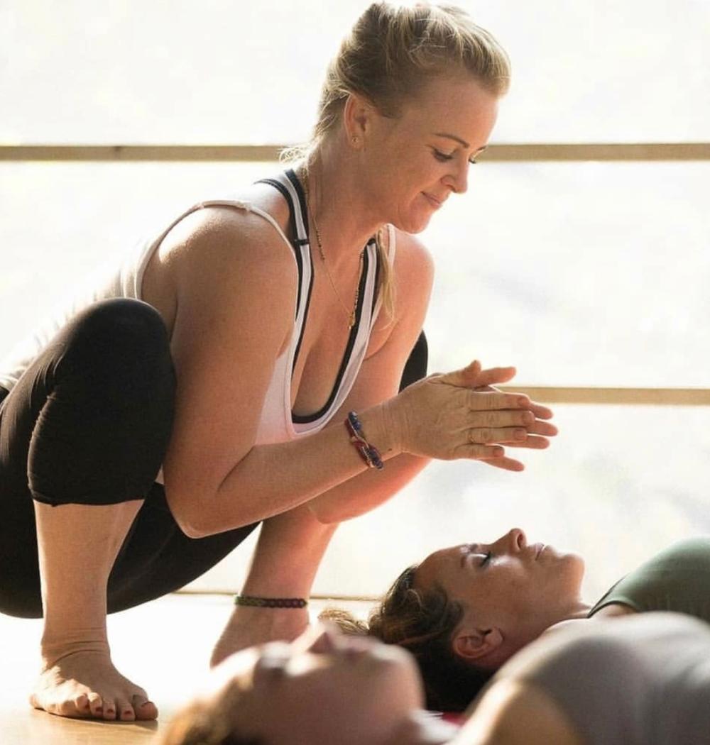 Yoga teacher Jenna Naik assisting in Shavasana