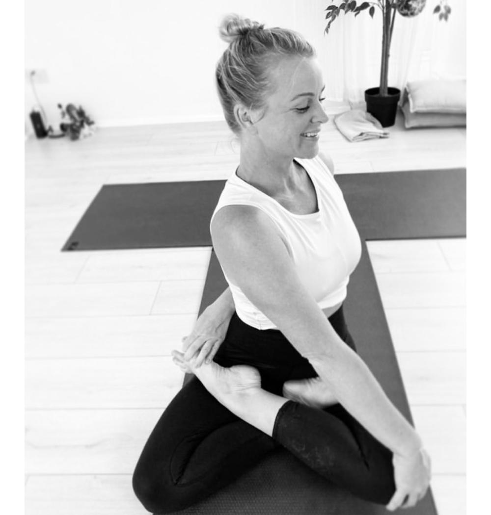 Yoga teacher Jenna Naik in twisted lotus pose