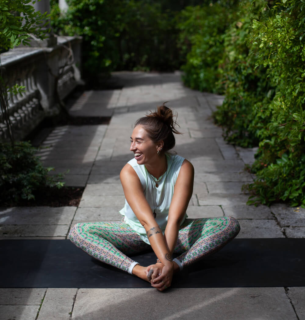 Yoga teacher Aimee Warren on yoga mat laughing