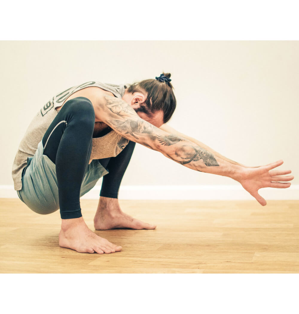 Yoga teacher Nate Thomas in Malasana